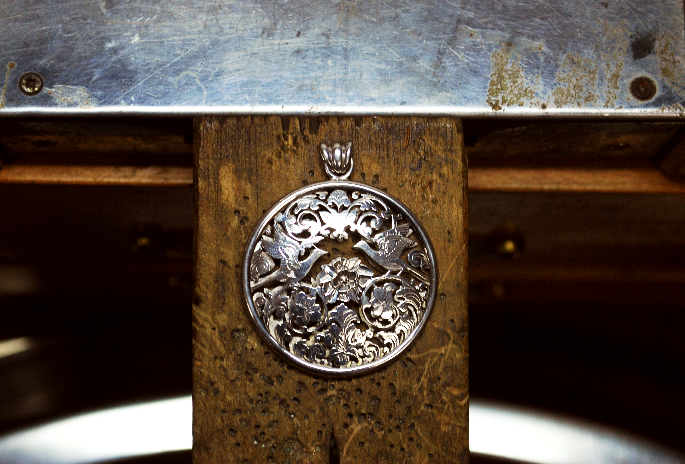 Piercing silver work piece on jeweller bench at Asimi Art studio in Hong Kong
