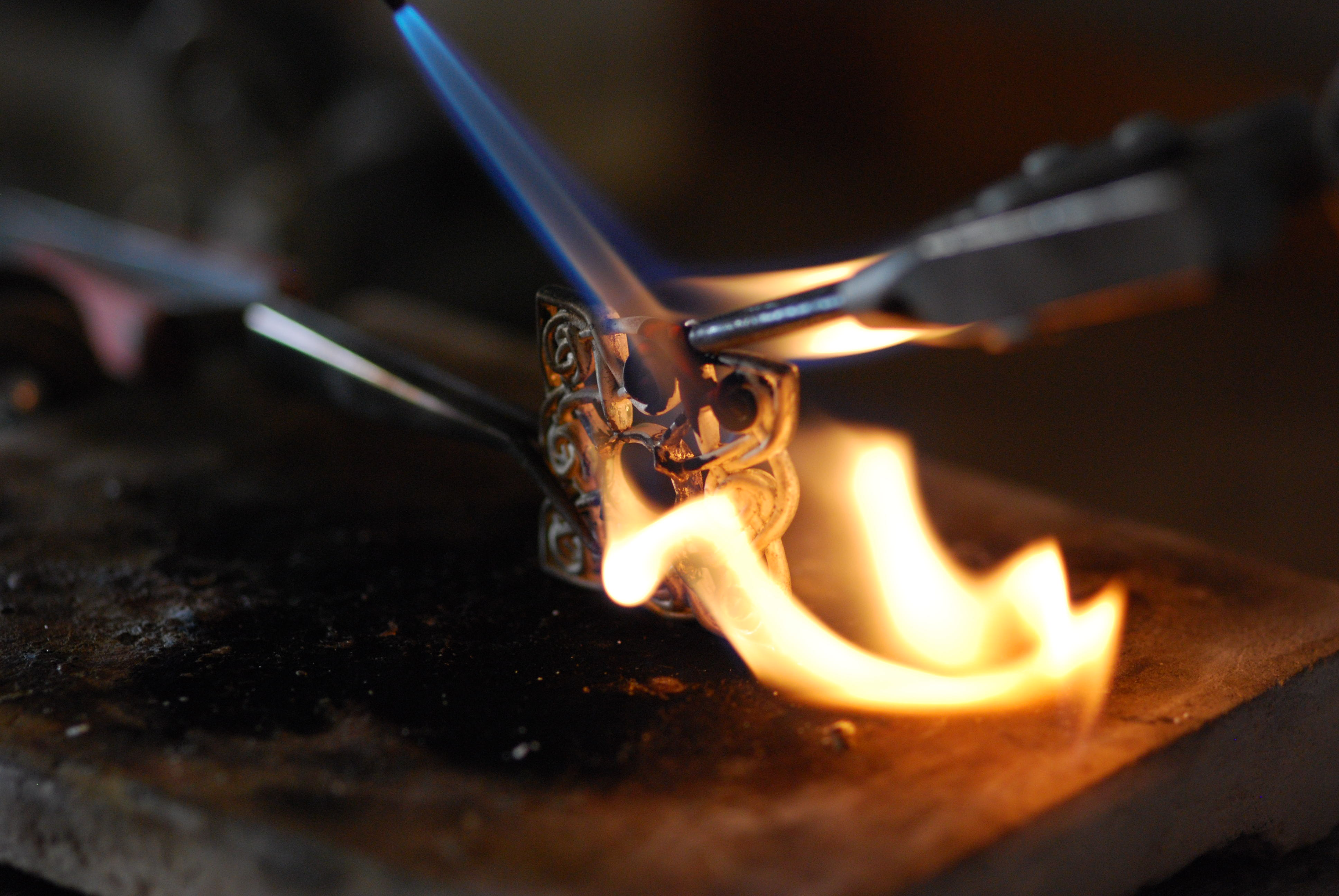 Torch firing sterling silver jewelry piece at jewelry bench